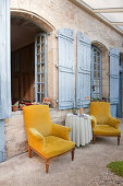 Two ochre-yellow armchairs on roofed terrace of Mediterranean country house