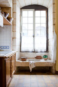 Tall lattice window in rustic country-house kitchen with old stone sink