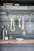 Kitchen utensils hanging from row of hooks on grey board wall