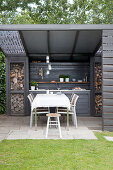 Dining area and outdoor kitchen in grey on roofed terrace