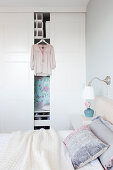 Blouse hung on whit wardrobe in bright bedroom