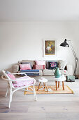 Collection of scatter cushions on sofa and rattan chair in living room in pastel shades