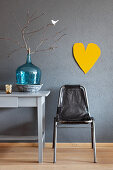 Vintage chair, branch in turquoise demijohn on desk and yellow heart on wall