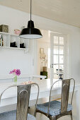 Metal chairs at the dining table with black industrial ceiling light