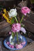 Ranunculus, hyacinths, Australian waxflowers and mimosa flowers in glass vase
