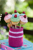 Mini cupcakes with raspberries in glass with crochet cover for garden party