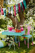 Garland above table set in bright colours for summer garden party
