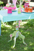 Old table with colourful fabric decoupage anc crocheted accessories in garden