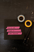 Pink masking tape with an address on a black envelope