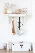 Storage jars and kitchen utensils on shelf above bread box