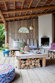 Fireplace with bench and table on a covered terrace with a wooden wall
