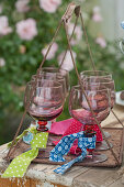 Wine glasses labelled with strips of various fabrics on tray