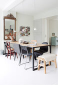 Long dining table with various chairs and antique mirror in bright dining area
