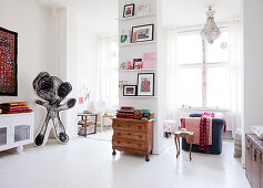 Open living room with cartoon character, antique dresser in front of a supporting wall, and sofa
