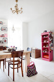 Solid wood table and pink shelving unit with dishes in the dining area