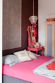 Mattress with pink sheets, next to it a matching vanity with a mirror in a bedroom