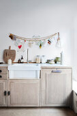 Wooden pearl necklace and greeting cards above the kitchen unit with sink