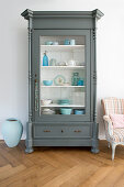 Crockery in shades of blue in grey, glass-fronted cabinet