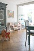 Dolls' pram in dining room with classic furniture and herringbone parquet floor