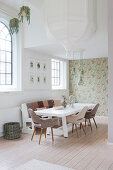 Dining room in white and earthy shades with high ceiling and lattice windows
