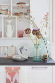 Artichoke flowers and branches of rose hips in vases decorating kitchen