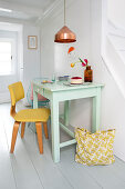 Yellow chair at green-painted kitchen table below copper pendant lamp