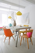 Metal table and various chairs in pastel shades