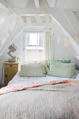 Scatter cushions on bed in converted attic with exposed wooden roof structure