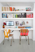 Vintage chairs in front of floating desk and shelves in niche