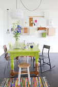 Green-painted dining table and various chairs in dining area