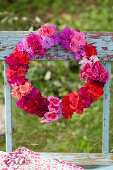 Wreath of geranium and azalea flowers in deep pink, red, lilac, pale pink and purple
