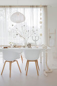 White shell chairs around festively decorated dining table