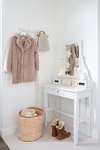White console table and winter clothing in festively decorated hallway
