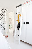 White ladder in front of white wardrobe in child's bedroom with black-and-white wallpaper