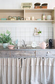 Wall-mounted shelves above base unit with wooden drawers and curtains in kitchen