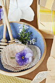Pansies, muffin liners, sprigs of rosemary, and honey dipper in a bowl
