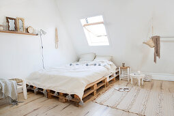 Bedroom in natural tones under the sloping roof with pallet bed