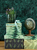 Boxes of paper stuck with fern motifs, mint blossoms and a small globe