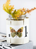 Butterfly motif on a paper sleeve around a jar with scented geranium leaves