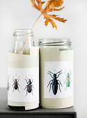 Paper cuffs affixed to screw-top jars with beetle motifs
