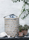 Laundry basket with a striped fabric sack in front of a white brick wall