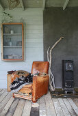 An old leather chair next to a wood-burning stove and a wall cupboard in a glass house