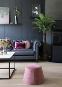 A dark sofa with pink cushions in front of a dark wall with a pouffe and a coffee table in the foreground