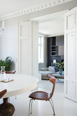 Round table with classic chairs in the dining area view through open double doors into the living room