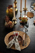 A place setting and candles on autumnally decorated table