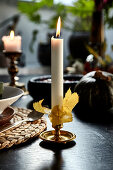 Candle decorated with autumn leaves