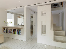 Open living room in white with spiral staircase and open kitchen