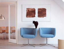 Two light blue armchairs under the abstract painting and a cat by the door