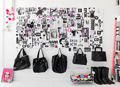 Black handbags hanging on the wall with collage in black and white
