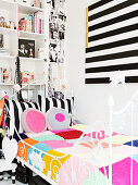 Black and white striped picture over a metal bed with a crochet pillow